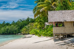 Bamboo Hut under Palm Trees of an Homestay on Gam Island, West Papuan, Raja Ampat, Indonesia