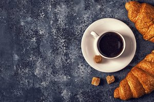 Croissants and coffee on a dark background