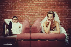 Happy newlyweds rest on the couches