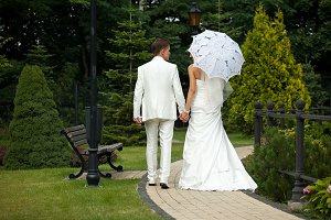 Groom holds bride's hand in a garden