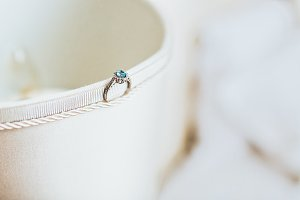 Emerald ring standing on side of textile box