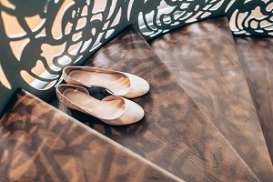Peach women's wedding shoes on wooden stairs with derative railings