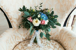 Wedding bouquet of fresh flowers for bride standing on armchair