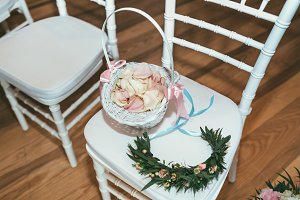 Basket with rose petals on white chair on wedding ceremony