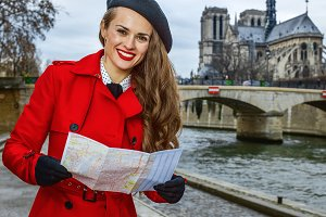 smiling traveller woman on embankment in Paris, France with map
