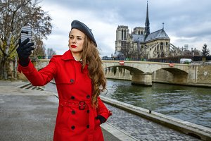 woman taking selfie with phone near Notre Dame de Paris in Paris