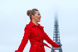 smiling trendy woman in front of Eiffel tower in Paris, France