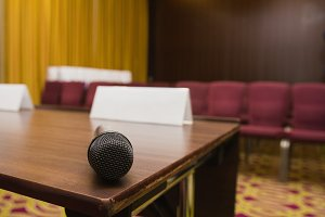 Close up view of microphone on table at press conference hall or seminar room background