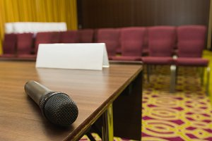 Microphone on table at press conference hall or seminar room background