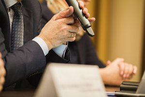 Businessman's holds microphone at conference or meeting, financial concept