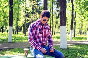 Man against a wall, with coffee talking on the phone, in the summer with glasses and shirt, happy smiling businessman.