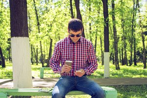 The man on the bench, with coffee or tea, read a message on the phone, in the summer in glasses and a shirt in the woods outdoors resting businessman.