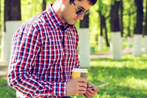 The man on the bench, with coffee or tea, read a message on the social networks on the phone, in the summer in glasses and a shirt in the woods outdoors resting businessman.