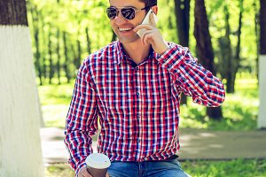 The man on the bench, with coffee or tea, talking on the phone, in the summer in glasses and a shirt in the woods outdoors resting happy smiling businessman.