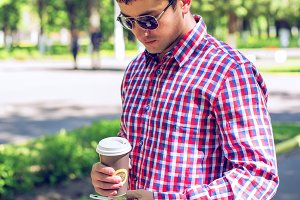 A man stands in the city, with coffee or tea, read a message on the social networks on the phone, in the summer in glasses and a shirt in the park outdoors resting businessman.