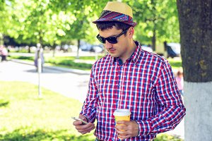 A man stands in the city, with coffee or tea, read a message on the social networks on the phone, in the summer in glasses and a shirt in the park outdoors resting businessman near the tree.