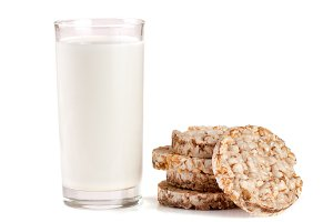 glass of milk with grain crispbreads isolated on white background