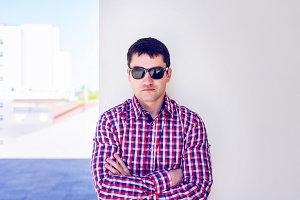 Man against a wall, serious look, self concept. In summer, the dark glasses and a shirt.