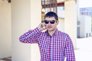 A man stands in the city in summer shirt, talking on the phone, businessman look important, serious intentions outdoors. The concept of emotion, dark glasses. Lifestyle young.