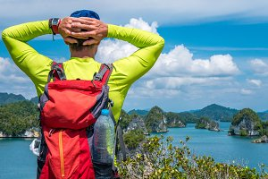 Traveler with Backpack enjoy the View over Roks in Kabui Bay near Waigeo. West Papuan, Raja Ampat, Indonesia