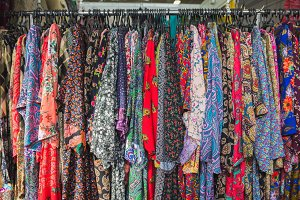 Close up colourful clothes hang on clothes rack in clothing store