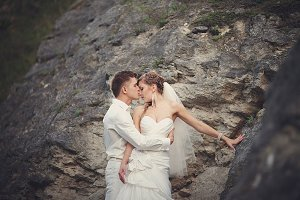Groom kisses bride between the rocks