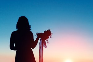 Silhouette of a bride holding bouquet in loneliness