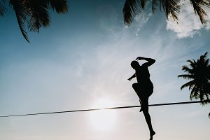 man balance on slackline on beach