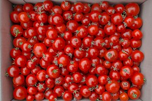 Red tomatoes background. Top view. Tomatoes in a box.