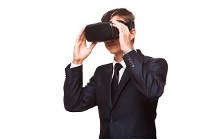 Young handsome businessman in black suit wearing virtual reality goggles., isolated on white background