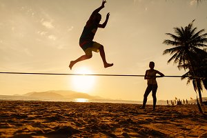 teenagers balancing on slackline
