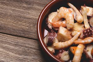 Tasty seafood salad in a clay pot. Horizontal shoot.