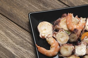 Tasty seafood salad on black plate. Horizontal shoot.