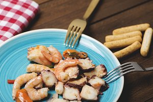 Tasty seafood salad with bread sticks. Horizontal shoot.