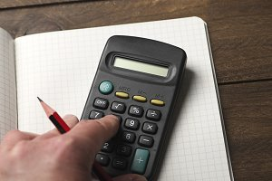 Hand holding a pencil while typing on a calculator lying on a pad. Horizontal shoot.