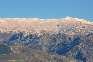 Snowy summits colored by the dust