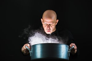 Cook looking into a big pan that smokes