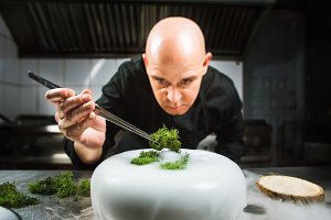 Chef is concentrated on preparing modern molecular dish with pincers and liquid nitrogen