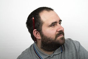 Young man with beard over weight and and with a pencil in his ear. Employee. Isolated.