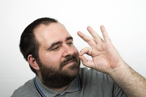 Young man with beard over weight and smiling makes a hand gesture. Isolated.