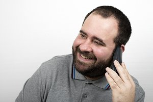 Young man with beard over weight and smiling talking on the phone. Isolated.