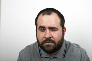 Young man with beard and over weight winks an eye to the camera. Isolated.