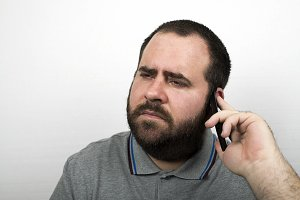 Young man with serious beard talking on a mobile phone. Isolated.
