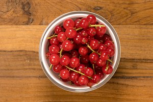 From above view of glass bowl of redcurrant fruit