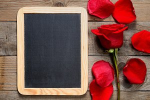 Blackboard and red rose