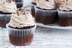 Chocolate cupcake with mousse cream icing on grunge white wooden background copy space