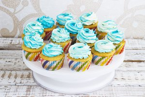 Festive cupcakes with cream in blue on a white wooden background