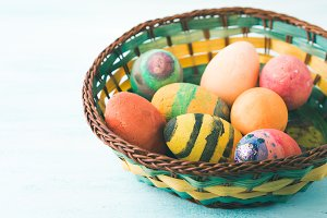 Colorful Easter eggs hand painted by kids in basket