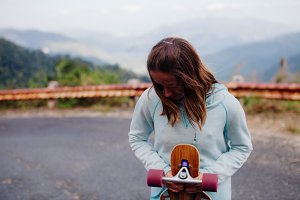 girl with longboard in mountains
