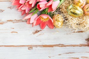Golden Easter Eggs and Pink Tulips on Light Background